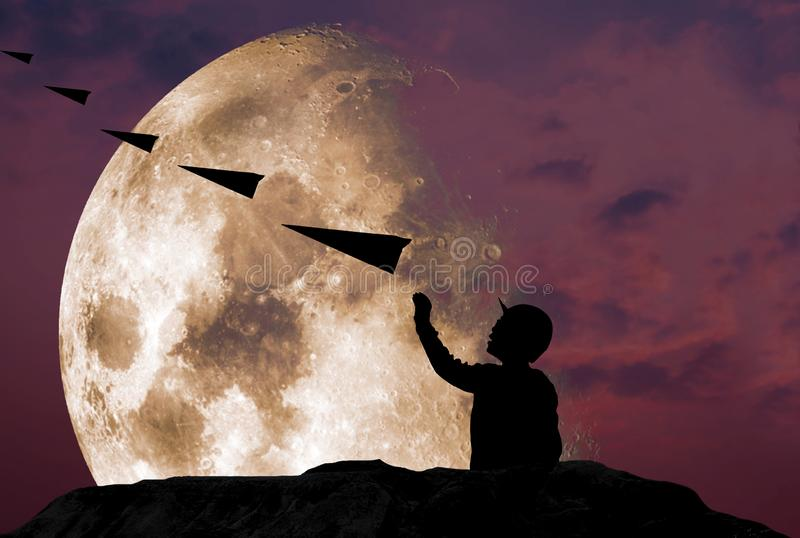 Silhouette of a boy standing, throwing a paper plane in air happily on a steep rocky cliff, with twilight skyline. A beautiful moon, Elements of this image royalty free stock photo