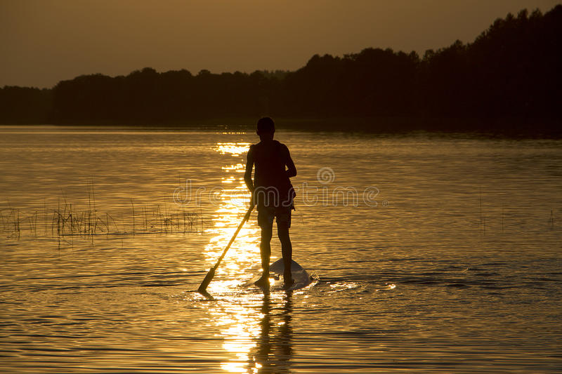 Silhouette boy on sup-board stand up paddle board in late evening during sunset stock photo
