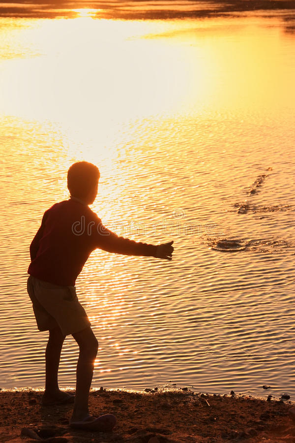 Silhouette of a boy throwing stones in a water, Khichan village, India stock image