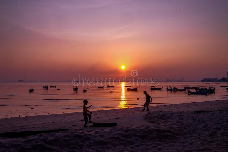 Silhouette of a boys enjoying the sunrsie at the beach stock photography