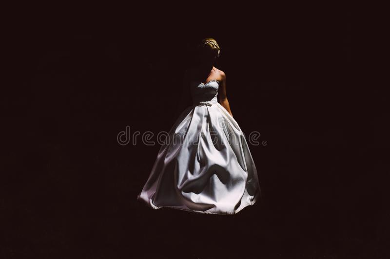 Silhouette of bride in a white dress on black background royalty free stock photos