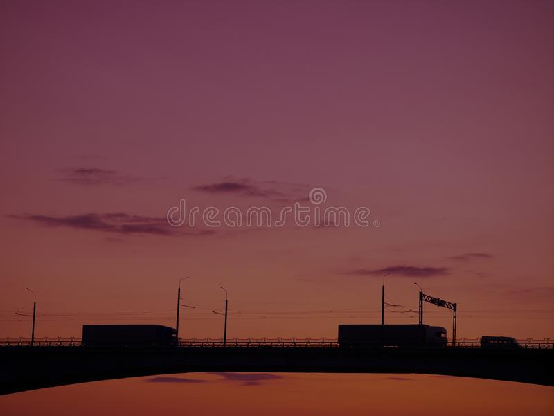 Silhouette of a bridge over a river at sunset, cityscape. Silhouette of a bridge with heavy vehicles over water over a river against a sunset, cityscape royalty free stock photo