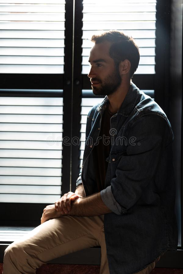 Silhouette of brunette attractive man standing in dark room at shadow blinds. Silhouette of brunette attractive man standing in dark room against the sunlight stock images