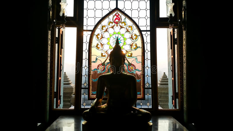 Silhouette buddha statue has flower and sun pattern stained gla stock photo