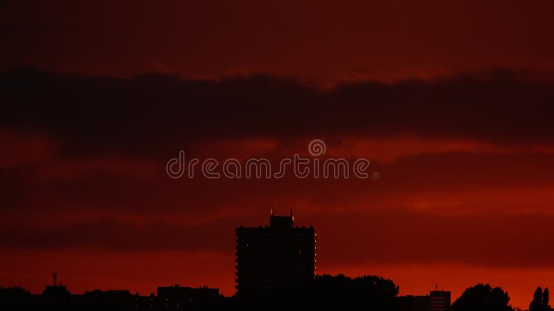 Silhouette of Building Structures Against Red Skies stock images
