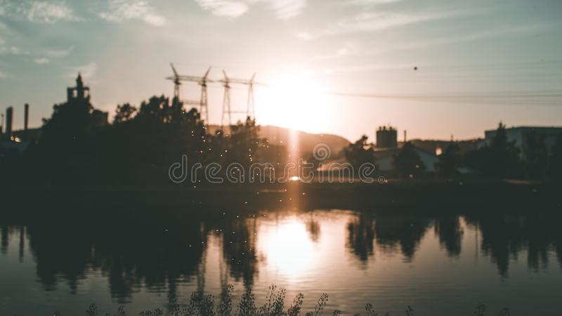 Silhouette of Building and Trees Near Body of Water during Golden Hour royalty free stock photos