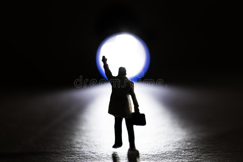 Silhouette of a business figurine waiving towards a small flashlight stock images