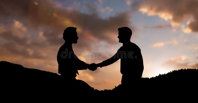 Silhouette business partners shaking hands on mountains during sunset stock image