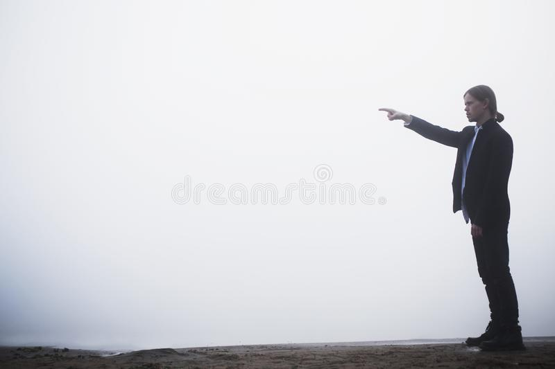 Silhouette of businessman on fog background. Man points to the side with his hand. Silhouette of man in costume. Business concept royalty free stock photography