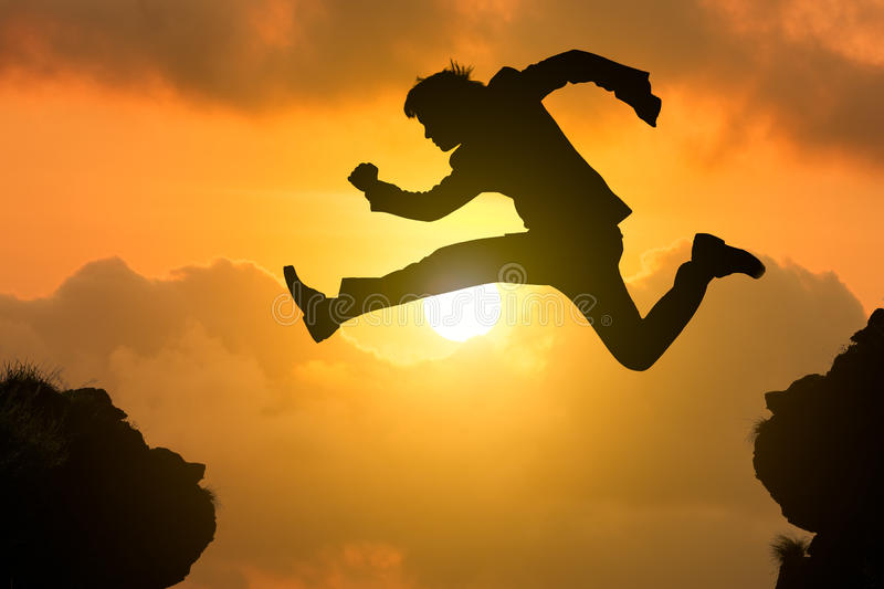 Silhouette businessman jump through the gap. With sunset, Business competition concept stock images
