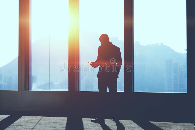 Silhouette of businessman is searching information on web page via mobile phone. Male CEO is standing in office interior against skyscraper window background stock photo