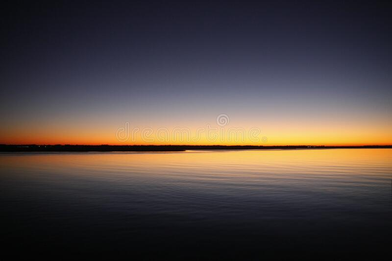 Silhouette of Calm Sea Under Blue and Orange Clear Sky during Sunset royalty free stock photo