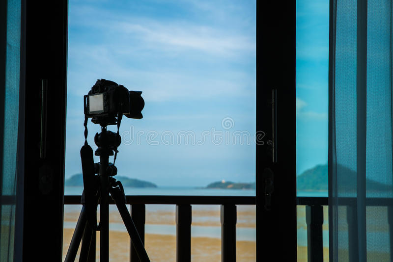 Silhouette camera on tripod at porch outside the room in the morning that can easy to shoot beautiful landscape. Silhouette camera on tripod at porch outside the royalty free stock image