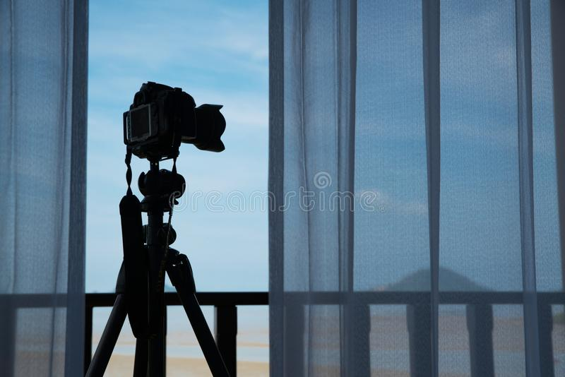 Silhouette camera on tripod at porch outside the room in the morning that can easy to shoot beautiful landscape. Silhouette camera on tripod at porch outside the royalty free stock images