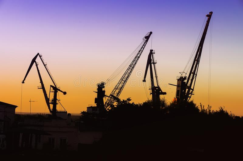 Silhouette of of cargo cranes. Port wharf landscape. Bright sunset, bright sky. Evening in the port royalty free stock photography