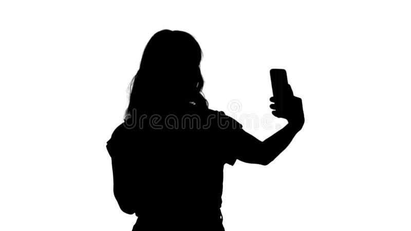 Silhouette Cheerful female blogger recording video to front camera of modern telephone while walking. stock image