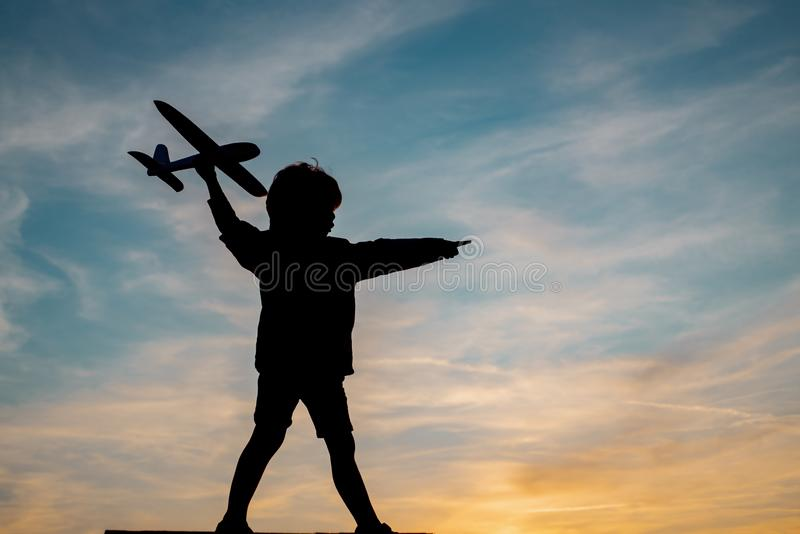 Silhouette of child with airplane in sunlight rays. Concept of dreams and travels. Dreams of flying planes. Silhouette of child with airplane in sunlight rays royalty free stock photo