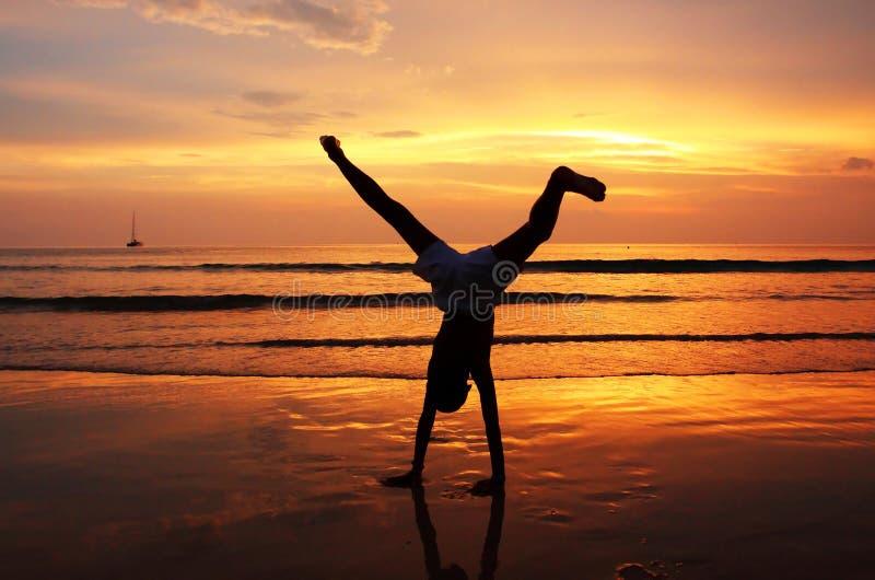 Silhouette of child on the beach. Beautiful twilight stock photo