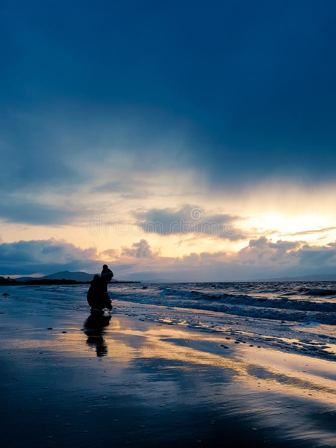 Silhouette of a child crouching at the edge of the sea stock image