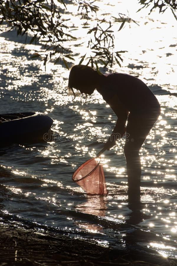 Silhouette of child fishing stock images