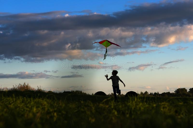 Silhouette of a child with a kite. Kite flying. child having fun flying a kite in the nature. the boy launches a kite. Sunset royalty free stock photography
