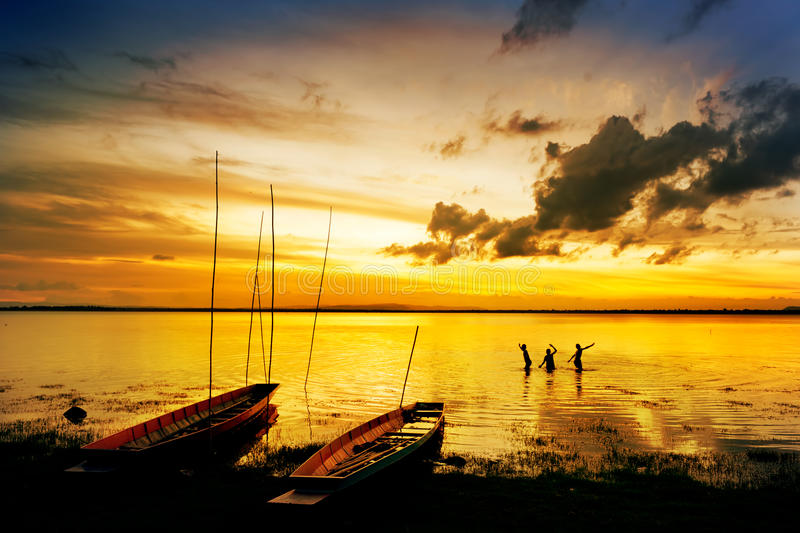Silhouette of children on boat. Silhouette of children on wood boat at sunset royalty free stock photo