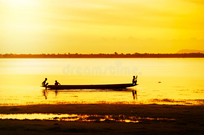 Silhouette of children on boat. Silhouette of children on wood boat at sunset royalty free stock image