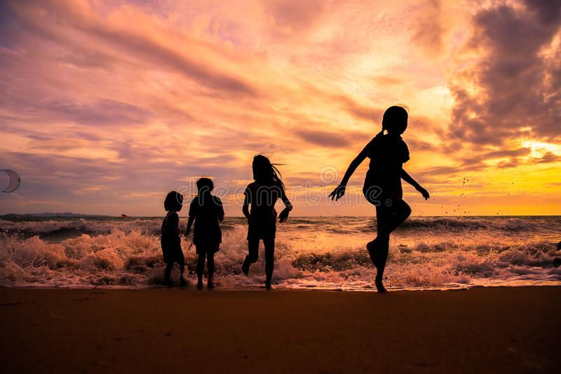 Silhouette children group enjoy playing on beach. Silhouette children group enjoy playing sea waves on the beach in sunset with beautiful twilight sky stock photos