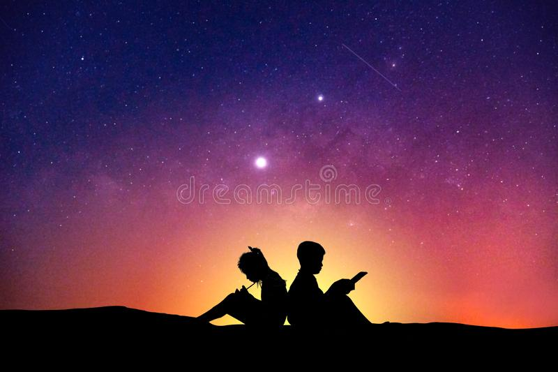 Silhouette of children reading a book at sky milky way royalty free stock photo