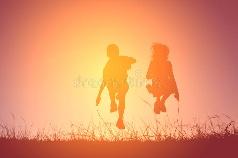 Silhouette children rope jumping on the sky sunset. Time on holiday happy and fun stock images