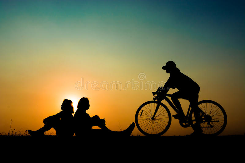Silhouette children on sunset. Silhouette of a children girls at the sunset time on meadow. someone sitting and riding a bike have a beauty yellow and blue sky royalty free stock photos