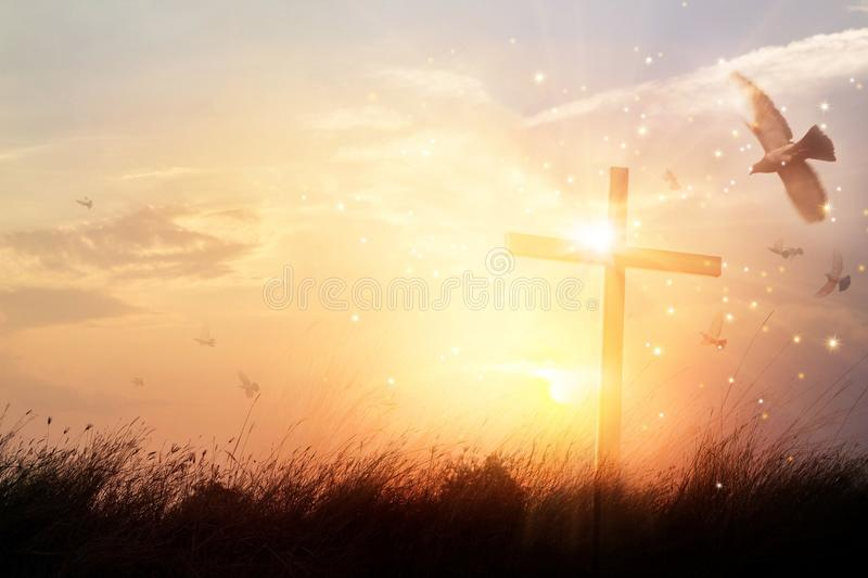 Silhouette christian cross on grass in sunrise background stock photo