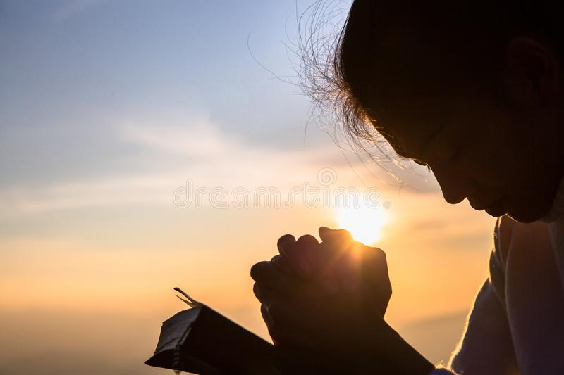 Silhouette of christian young woman praying with a  cross and open the bible at sunrise, Christian Religion concept background royalty free stock photo