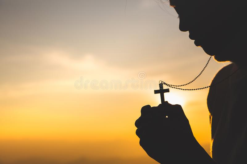 Silhouette of christian young woman praying with a  cross at sunrise, Christian Religion concept background royalty free stock photos