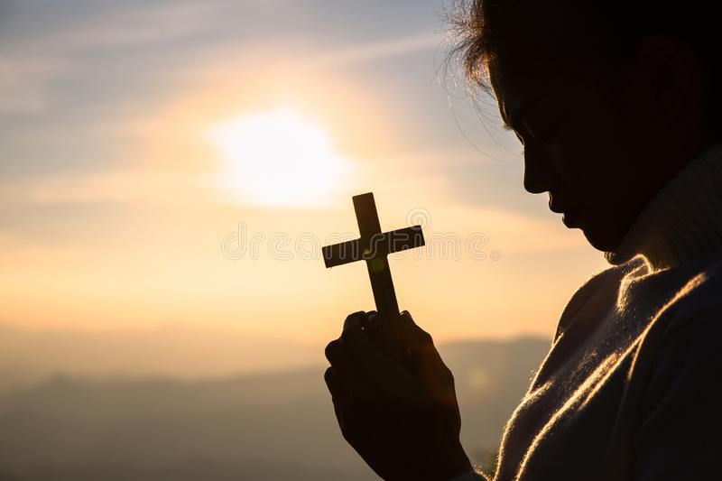Silhouette of christian young women praying with a  cross at sunrise, Christian Religion concept background royalty free stock image