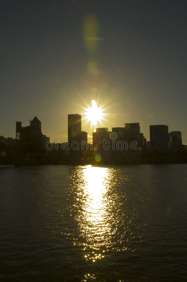 Silhouette of a city. The setting sun creates a silhouette of Portland, Oregon as the water sparkles with reflections of the sunlight royalty free stock image