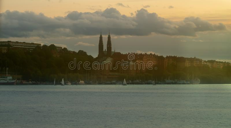 Silhouette of a city at dusk over water at sunset stock photography