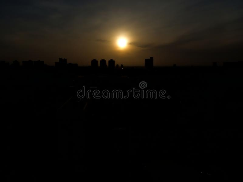 Silhouette of city in the morning. Silhouette cityscape of the dawn with a sky, cloud and the circle sun stock images