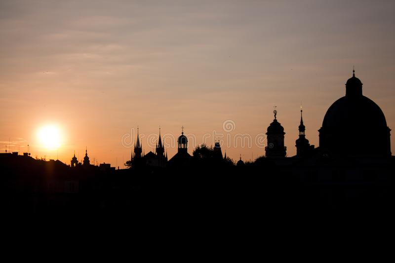 Silhouette of city Prague at sunrise or sunset. Photo of city Praha silhouette at sunrise or sunset with sun on horizon. Panoramic view of spires, domes and royalty free stock photo