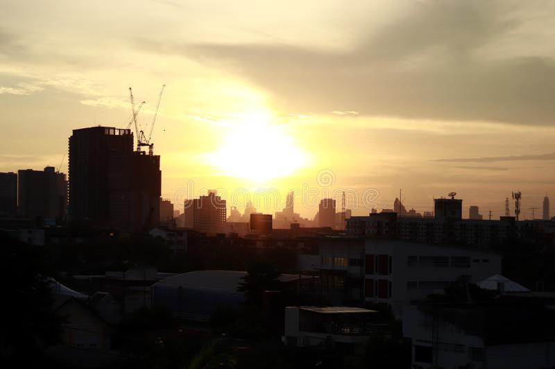 Silhouette city scape over sunrise golden light shine, silhouette urban in orange sky sunset evening time, city over sunrise royalty free stock images