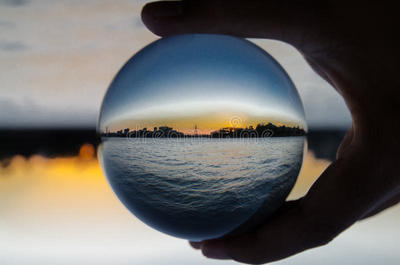 Silhouette of cityscape with dark ocean view photography in clear crystal glass ball. stock photography