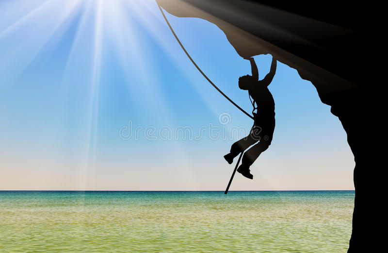 Silhouette climber climbing a mountain royalty free stock images
