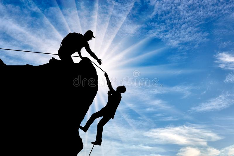 Silhouette of a climber who helps to climb the top of a man, throws him a rope and holds out his hand stock photos