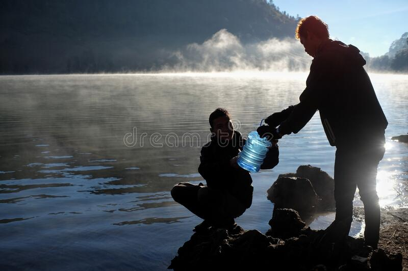 Silhouette of climbers taking clean water from Lake Ranu Kumbolo in the morning. Lumajang, Indonesia, 08/17/2019: Silhouette of climbers taking clean water from stock photos