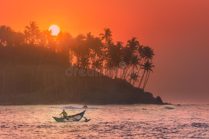 Tropical beach on sunset with fishermen and sea royalty free stock photography