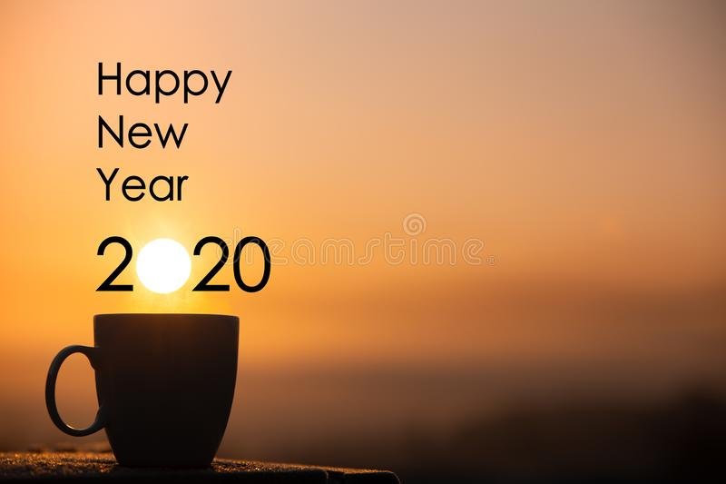 Silhouette coffee cup with happy new year 2020 text on a sunrise background royalty free stock photo