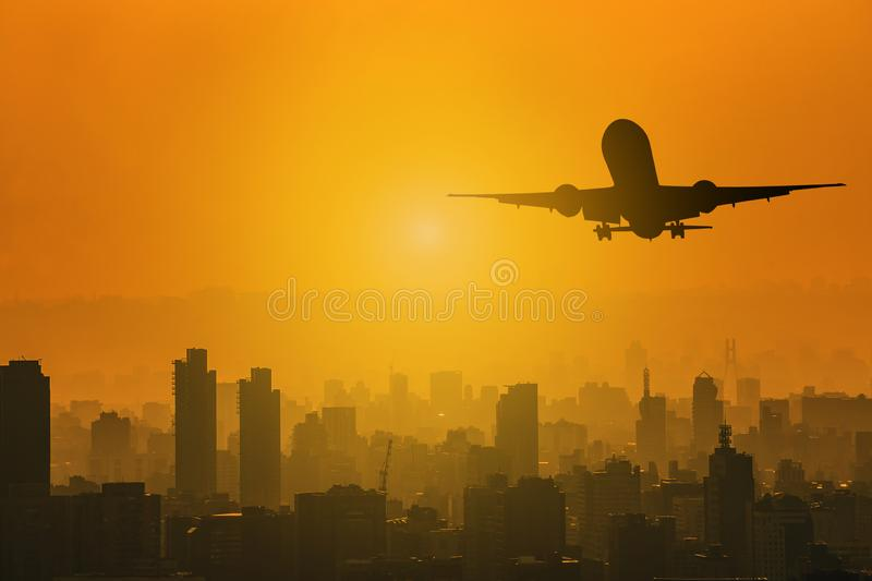 Silhouette of commercial plane flying over a city during with skylight sunset with copy space for text stock photo