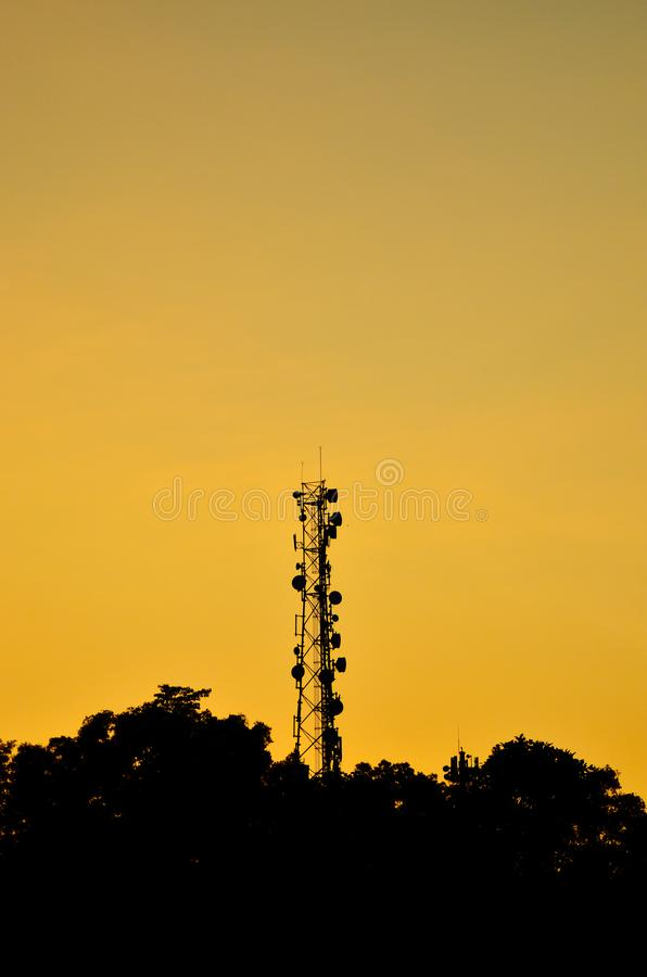 Silhouette of a communication tower among the trees. Silhouette view of telecommunication tower with dishes attached to it, during sunrise stock photography