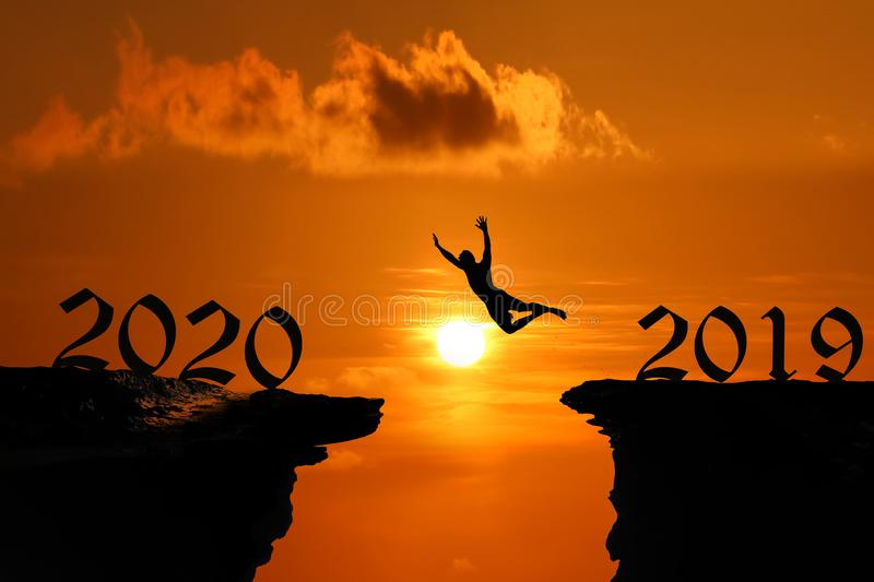 The Silhouette concept of new year 2020, Man jumping and climbing in the cave or high cliffs at a red sky sunset royalty free stock photography