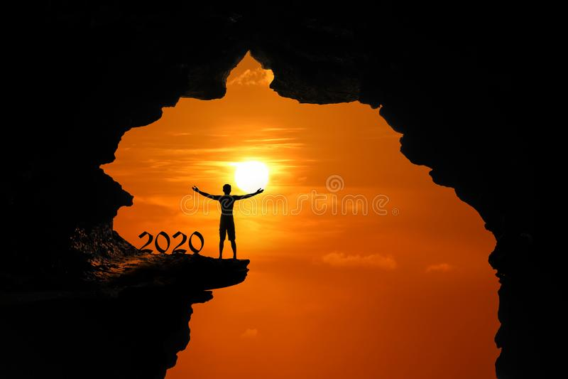 The Silhouette concept of new year 2020, Man standing and climbing in the cave or high cliffs at a red sky sunset royalty free stock image